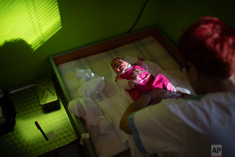 A nurse dresses a baby at the Kezmarok hospital on Nov. 16. 2018, in Kezmarok, Slovakia. (AP Photo/Felipe Dana)