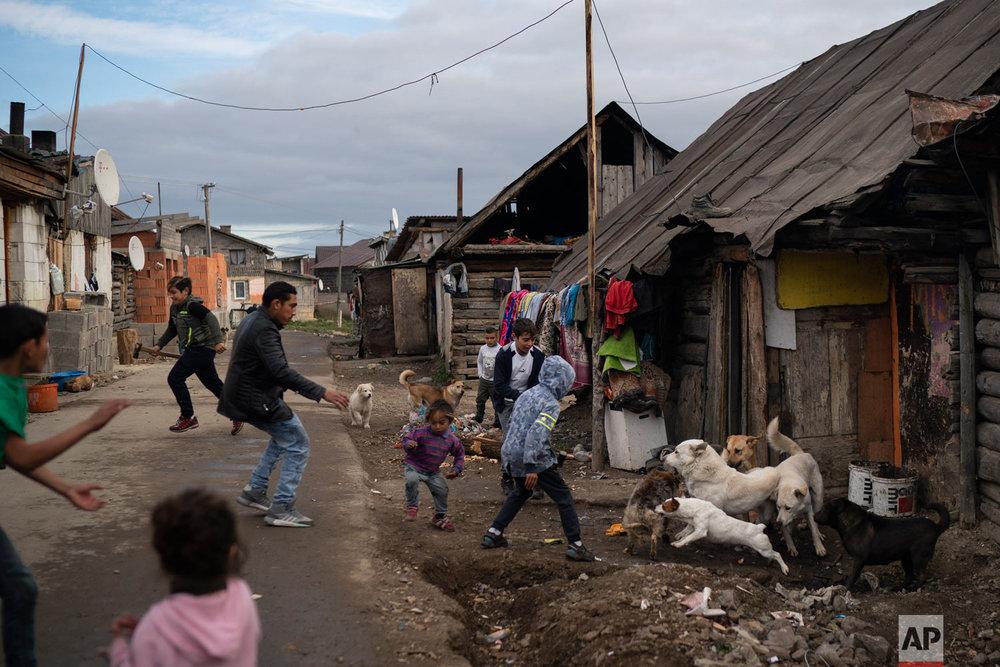 People run during a dog fight in a village on Nov. 12, 2018, near Kezmarok, Slovakia. (AP Photo/Felipe Dana)