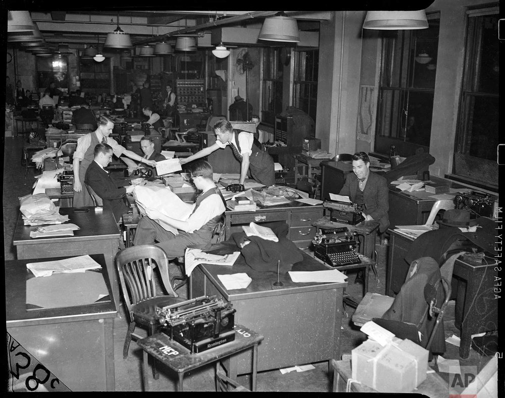 This undated photo shows reporters working at the 383 Madison Ave. office in New York. (AP Photo/Corporate Archives)