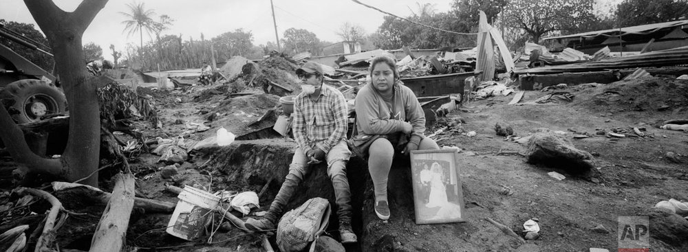 Marlene Vazquez, right, rests next to her cousin Silas Vazquez, as she holds a portrait of their cousins, killed by the Volcan de Fuego, or Volcano of Fire eruption, in San Miguel Los Lotes, Guatemala on June 13, 2018. (AP Photo/Rodrigo Abd)