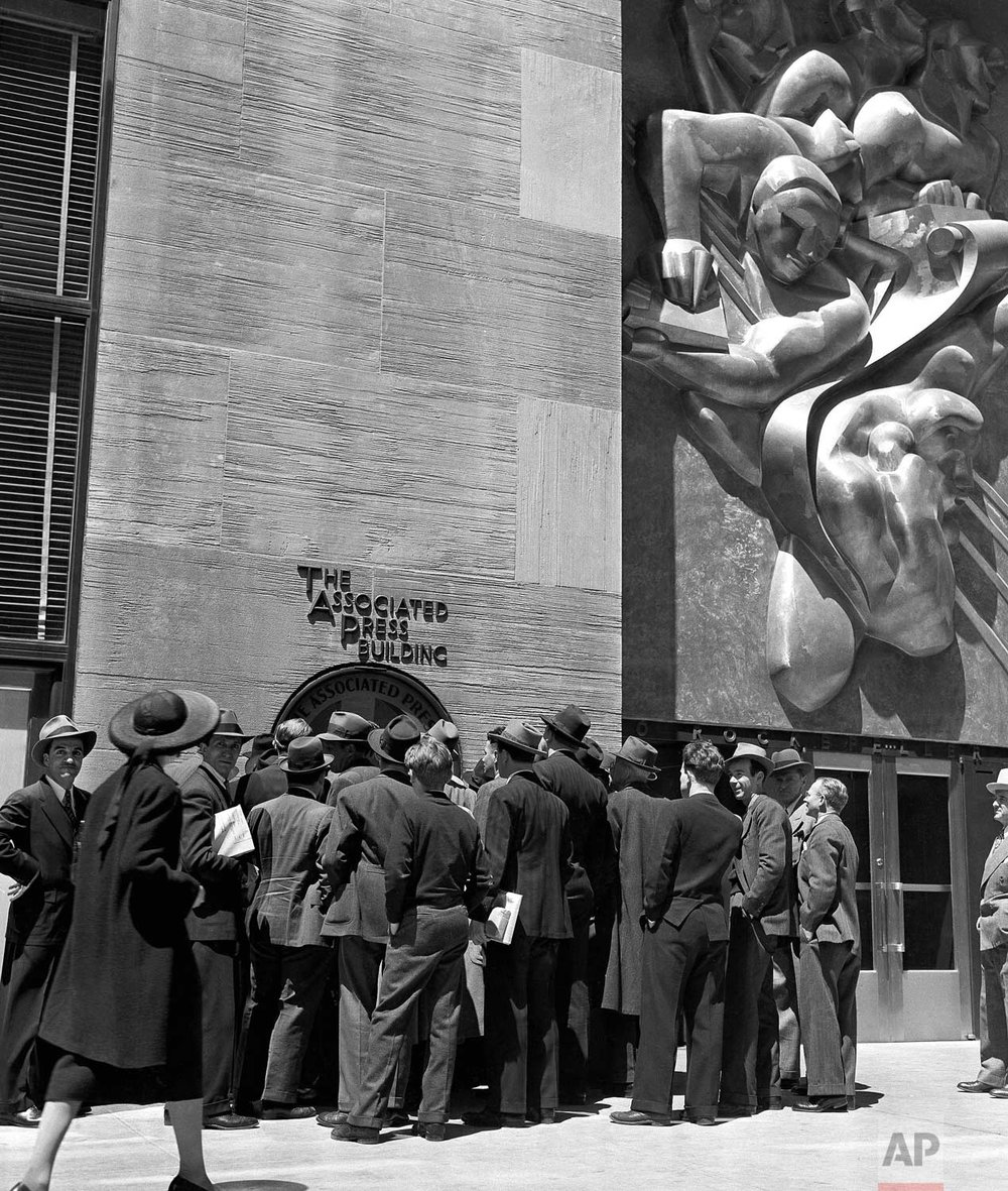 People surround the teletype machine at the Associated Press Building on Rockefeller Plaza in New York City, May 10, 1940. (AP Photo/Robert Kradin)
