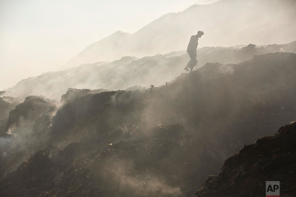 In this Monday, Dec. 10, 2018 photo, a ragpicker man walks amidst the smoke to search recyclable materials at a garbage dumping site on the outskirts of Gauhati, India. (AP Photo/Anupam Nath)