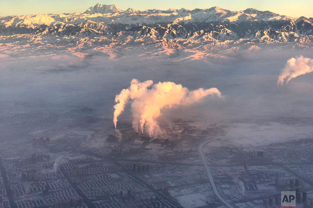 In this photo taken Wednesday Dec. 5, 2018 from a plane, smoke stacks are seen near the city of Urumqi China's northwestern region of Xinjiang. (AP Photo/Ng Han Guan)