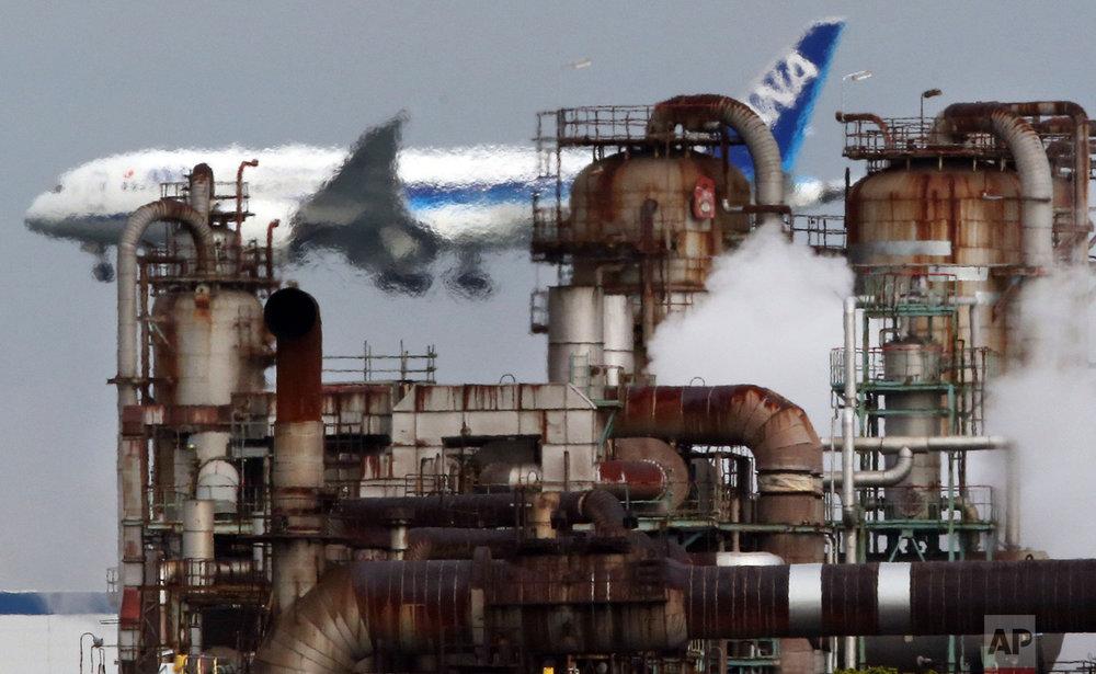 In this Thursday, Dec. 13, 2018 photo, a passenger plane prepares for landing near an oil refinery in Kawasaki, southwest of Tokyo. (AP Photo/Koji Sasahara)