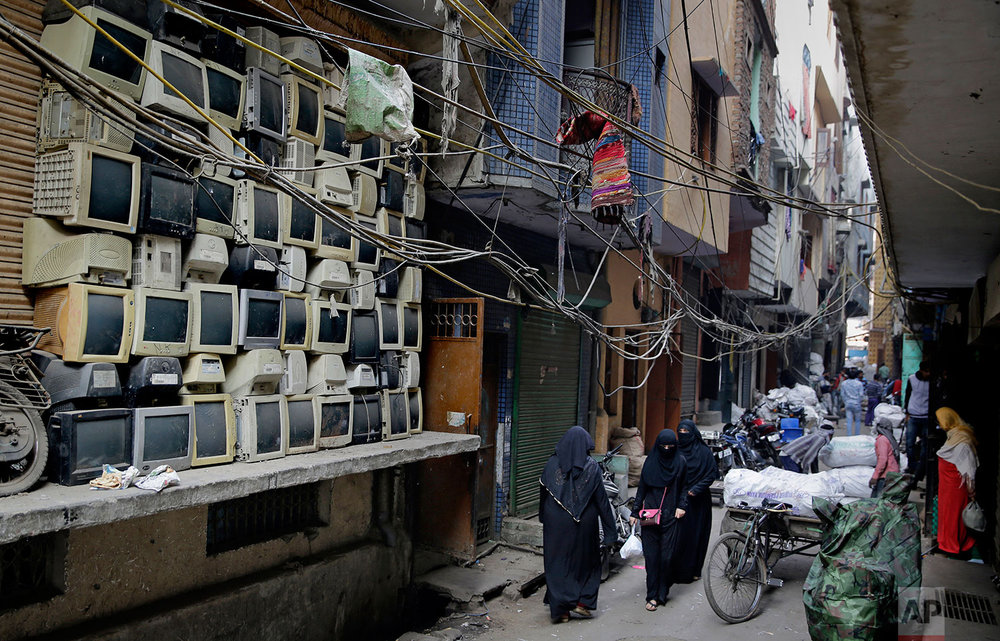 In this Saturday, Dec. 8, 2018 photo, discarded television sets are stacked up in an alleyway in an area known for storing electronic waste in New Delhi, India. (AP Photo/Altaf Qadri)