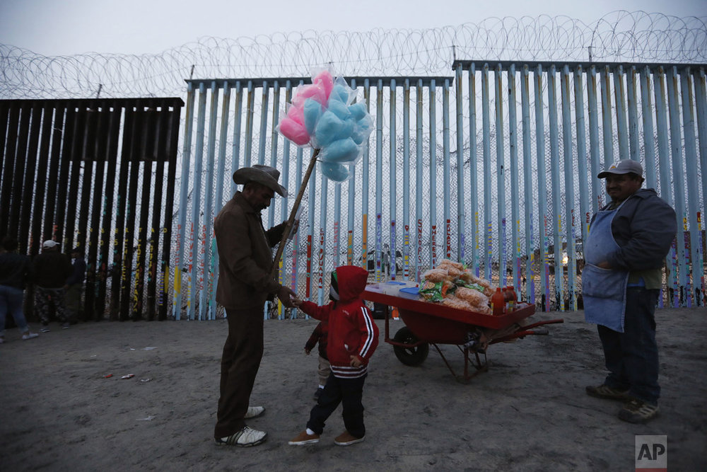 A Honduran migrant boy tries to buy cotton candy from a vendor, but doesn't have enough money, as migrants visit the U.S. border wall to look for opportunities to cross, at the beach in Tijuana, Mexico, on Sunday, Dec. 9, 2018. Discouraged by the long wait to apply for asylum through official ports of entry, many Central American migrants from recent caravans are choosing to cross the U.S. border wall illegally and hand themselves in to Border Patrol agents to request asylum. (AP Photo/Rebecca Blackwell)