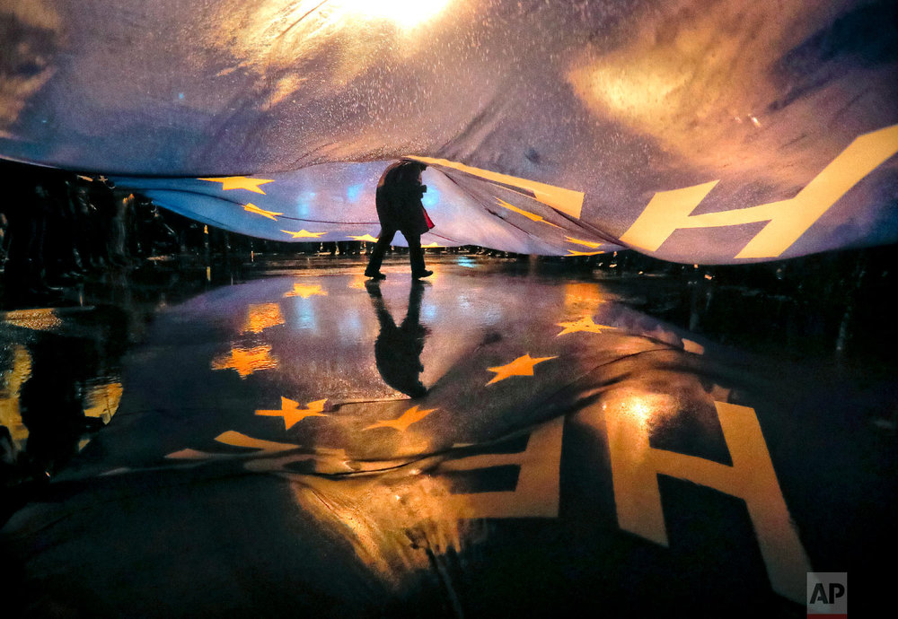 """A protester walks under a large European Union flag bearing the words """"Here_Now"""" during a protest outside the parliament building in Bucharest, Romania. (AP Photo/Vadim Ghirda)"""