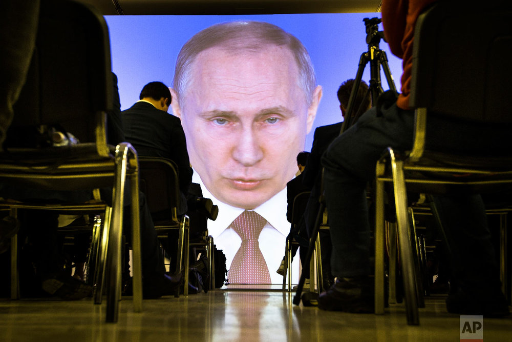 Journalists watch as Russian President Vladimir Putin gives his annual state of the nation address in Manezh in Moscow, Russia on March 1, 2018. (AP Photo/Alexander Zemlianichenko)