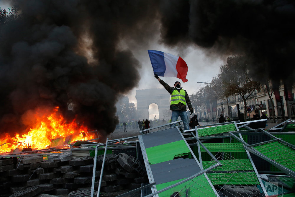 A demonstrator waves the French flag onto a burning barricade on the Champs-Elysees avenue during a demonstration against the rising of the fuel taxes in Paris on Nov. 24, 2018. (AP Photo/Michel Euler)