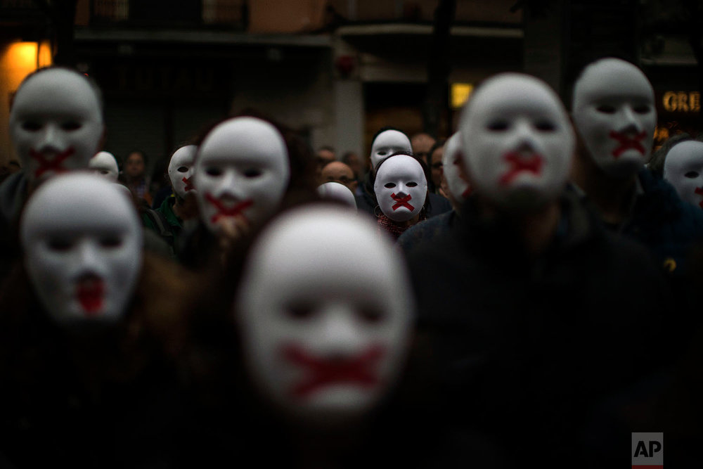 People wear white masks in support of Catalonian politicians jailed on charges of sedition and condemning the arrest of Catalonia's former president, Carles Puigdemont, in Germany, during a protest in Figures, Spain on April. 5, 2018. (AP Photo/Emilio Morenatti)