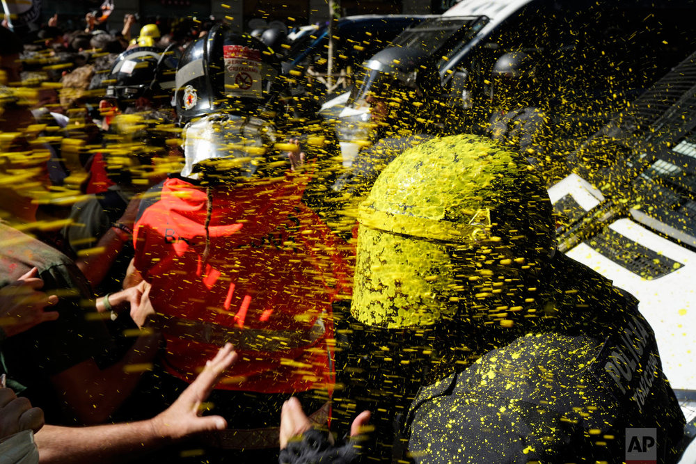 Pro-independence demonstrators throw paint at Catalan police officers during clashes in Barcelona, Spain on Sept. 29, 2018. (AP Photo/Daniel Cole)