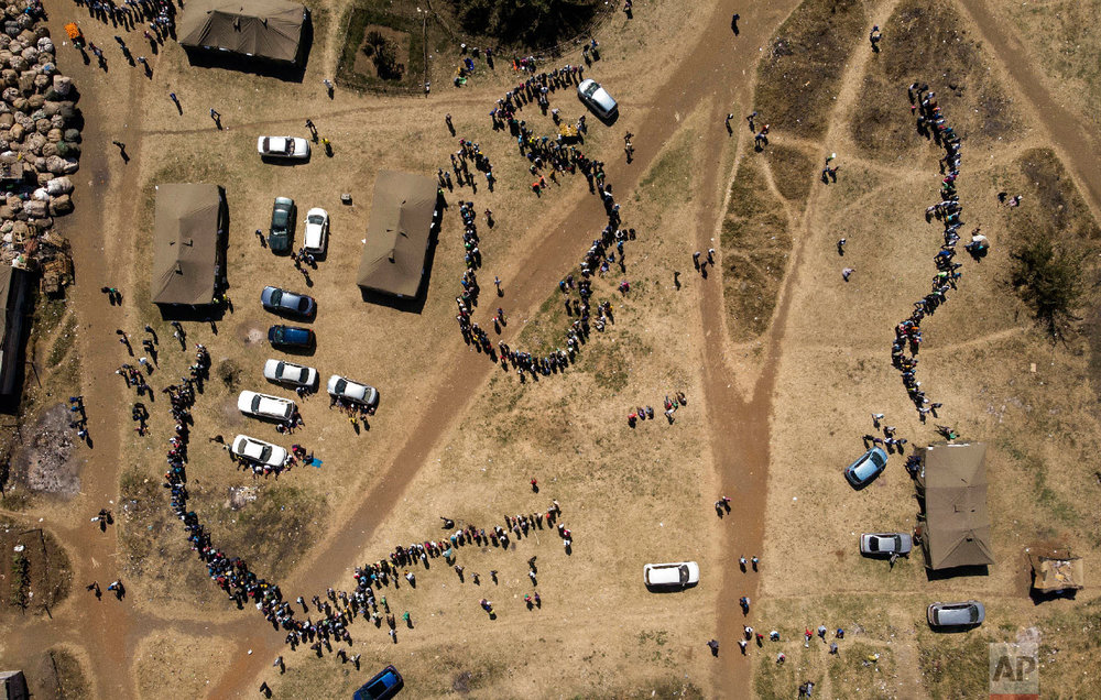 People wait in a queue to cast their vote at a polling station in Harare, Zimbabwe on July 30, 2018. Zimbabweans on Monday voted in their first election without Robert Mugabe on the ballot, a contest that could bring international legitimacy and investment or signal more stagnation if the vote is seriously flawed. (AP Photo/Bram Janssen)