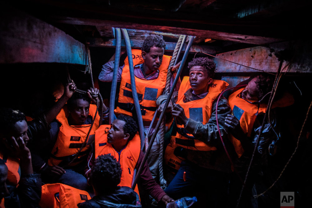 Sub-Saharan refugees and migrants, mostly from Eritrea, wait to be rescued by aid workers of Spanish NGO Proactiva Open Arms, in the lower deck of a wooden as they were trying to leave the Libyan coast and reach European soil, 34 miles north of Kasr-El-Karabulli, Libya on Jan. 16, 2018. (AP Photo/Santi Palacios)