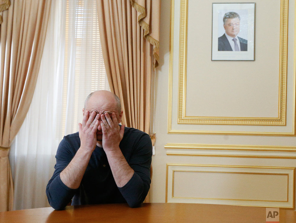 Russian journalist Arkady Babchenko holds his face during an interview with foreign media, with the portrait of Ukrainian President Petro Poroshenko, right in the background, in Kiev, Ukraine on May 31, 2018. (Valentyn Ogirenko/Pool Photo via AP)