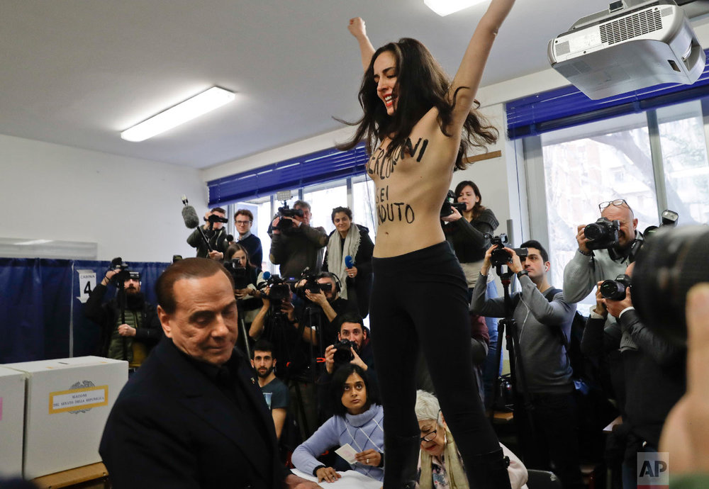 """A topless woman with writing on her body reading """"Berlusconi you expired"""" protests in front of Italian former premier and leader of Forza Italia (Go Italy) party Silvio Berlusconi at a polling station in Milan, Italy on March 4, 2018. (AP Photo/Luca Bruno)"""