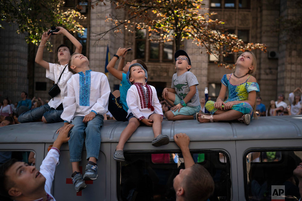 Children look up as military aircrafts fly above the city center during a military parade to celebrate Independence Day in Kiev, Ukraine on Aug. 24, 2018. (AP Photo/Felipe Dana)