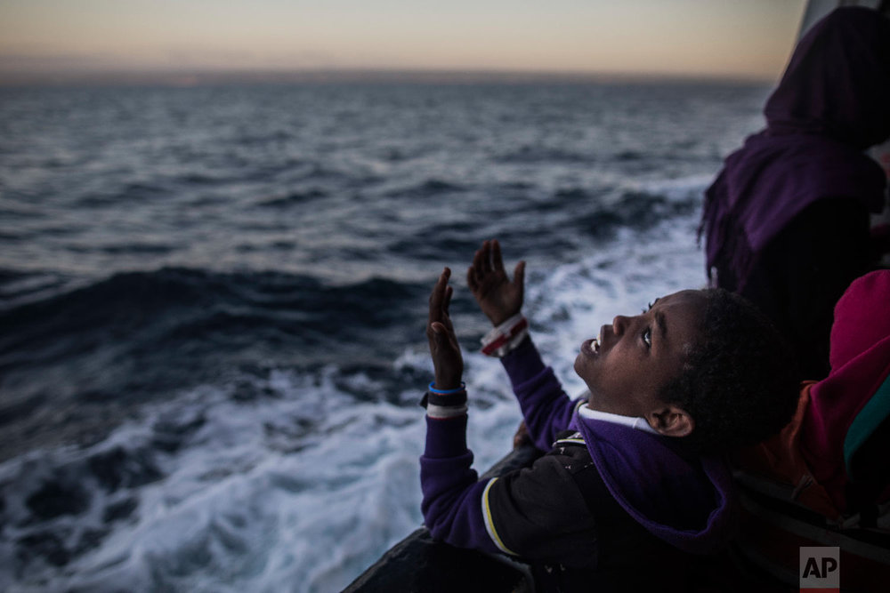 A child from Eritrea sings to celebrate his arrival to Europe aboard the Spanish NGO Proactiva Open Arms rescue vessel near Pozzallo, Sicily, Italy on Jan. 18, 2018. (AP Photo/Santi Palacios)
