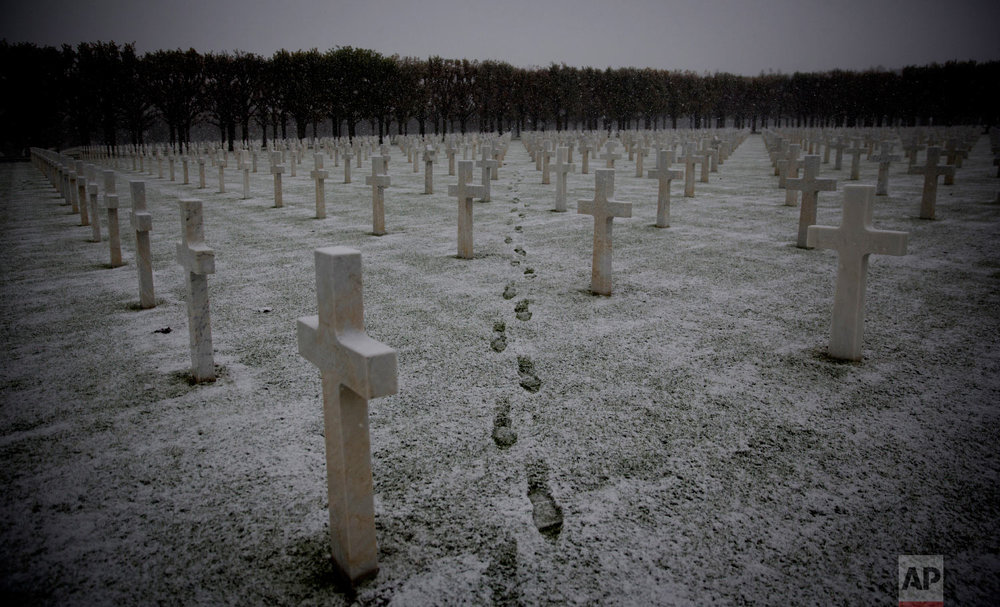 Footsteps are seen as the snow falls at the Meuse-Argonne American WWI cemetery in Romagne-Sous-Montfaucon, France on Oct. 30, 2018. (AP Photo/Virginia Mayo)