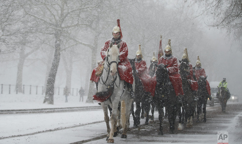 Members of the Household Cavalry return to their barracks as snow falls in London. Britain, which is buffered by the Atlantic Ocean and tends to have temperate winters, saw heavy snow in some areas that disrupted road, rail and air travel and forced hundreds of schools to close on Feb. 28, 2018. (AP Photo/Alastair Grant)