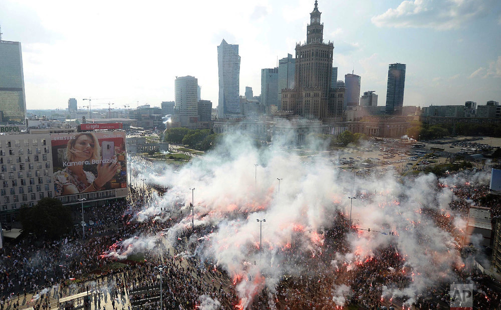 Warsaw residents stand at attention with national flags and flares to observe a minute of silence for the fighters and victims of the 1944 Warsaw Rising against the Nazi German occupiers, on the 74th anniversary of the revolt, in downtown Warsaw, Poland on Aug. 1, 2018. (AP Photo/Czarek Sokolowski)