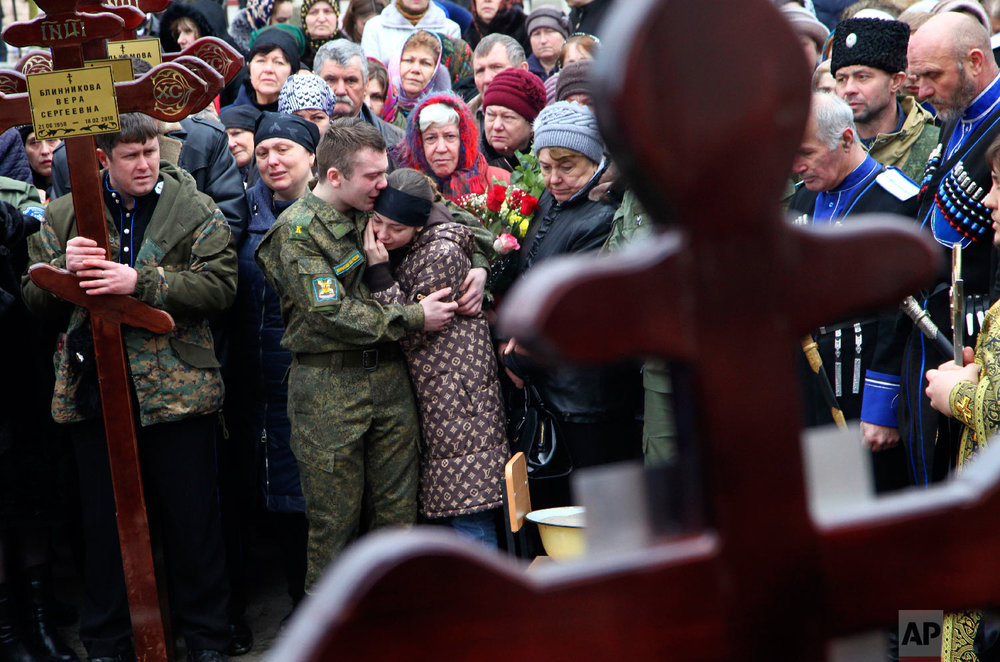 Family and friends of victims of the deadly attack on churchgoers in Russia's predominantly Muslim Dagestan region, attend a funeral service in Kizlyar, Russia on Feb. 20, 2018. (AP Photo/Musa Sadulayev)