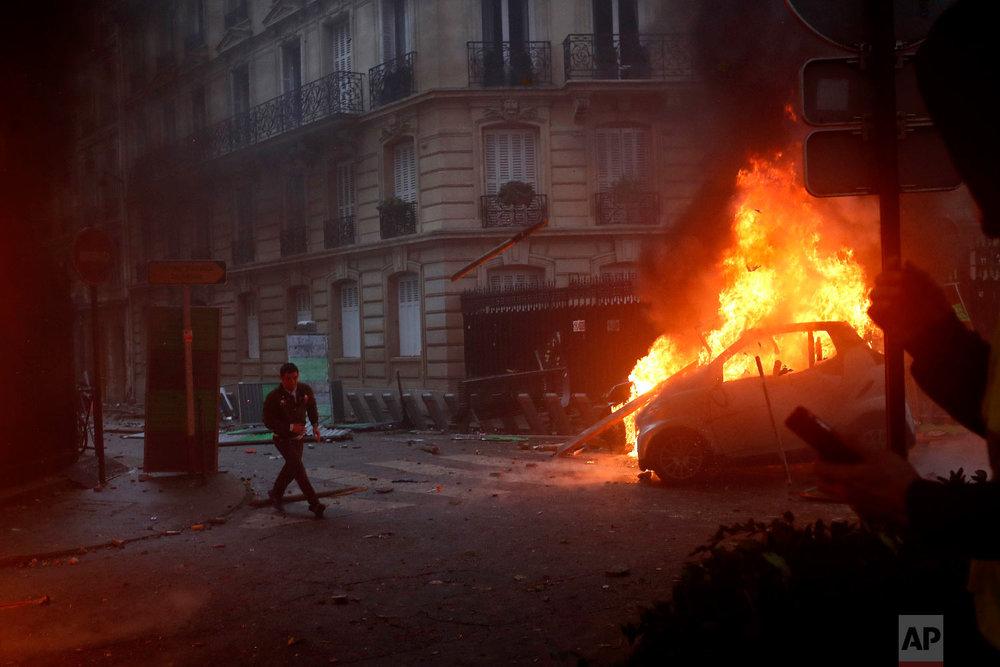 A demonstrator runs pas a burning car during a demonstration in Paris on Dec. 1, 2018. (AP Photo/Thibault Camus)