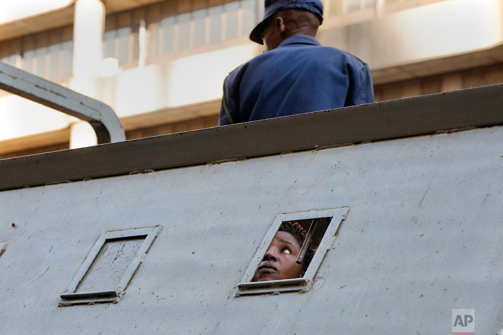 A supporter of Zimbabwean's main opposition party MDC, who was arrested following clashes, is seen detained in a police vehicle outside the MDC headquarters, in Harare on Aug. 2, 2018. (AP Photo/Jerome Delay)