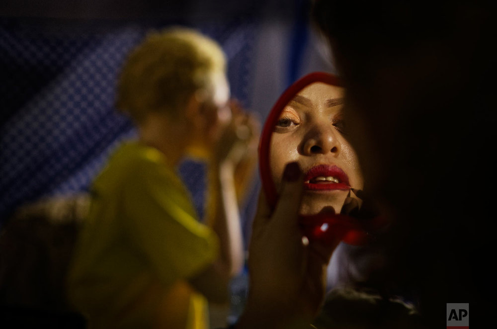 """A contestant checks her makeup in a mirror as she prepares to perform in the """"Mr. & Miss Albinism East Africa"""" contest, organized by the Albinism Society of Kenya, in Nairobi, Kenya on Nov. 30, 2018. (AP Photo/Ben Curtis)"""