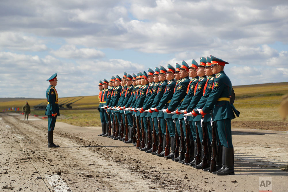 """A Russian honor guard prepares to take a part in a parade prior to a military exercises on training ground """"Tsugol"""", about 250 kilometers (156 miles ) south-east of the city of Chita during Vostok 2018 in Eastern Siberia, Russia on Sept. 13, 2018. (AP Photo/Sergei Grits)"""