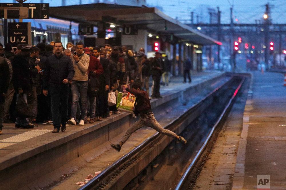 A passenger crosses railroad tracks at rush hour at Gare de Lyon train station, in Paris, France, as union stage a mass strike on April 3, 2018. (AP Photo/Francois Mori)