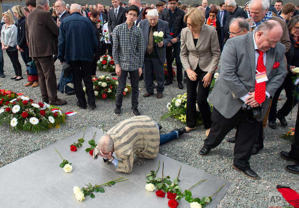 Former Nazi concentration camp survivor Alexander Bytschok of Kiev, Ukraine, mourns on a plain metal plaque during the commemoration ceremonies for the 73th anniversary of the liberation of the former Nazi concentration camp Buchenwald near Weimar, Germany on April 15, 2018. On 11th April 1945, units of the 3rd US Army reached Ettersberg Hill. (AP Photo/Jens Meyer)