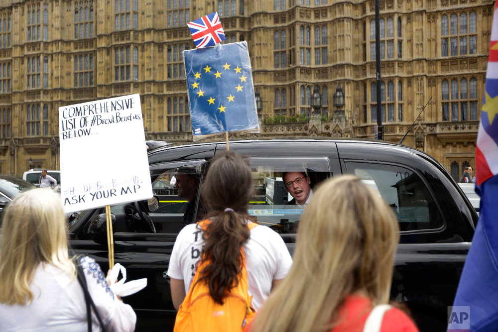 A man in a passing taxi shouts his disagreement at anti-Brexit, pro-EU supporters protesting backdropped by the Houses of Parliament in London on June 20, 2018. (AP Photo/Matt Dunham)