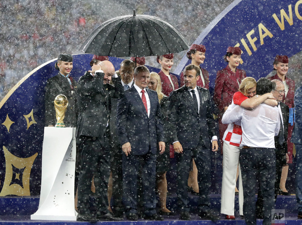 From left are, FIFA President Gianni Infantino, Russian President Vladimir Putin, French President Emmanuel Macron and Croatian President Kolinda Grabar-Kitarovic hugging CVroatias head coach Zlatko Dalic as heavy rain falls during the award ceremony at the end of the final match between France and Croatia at the 2018 soccer World Cup in the Luzhniki Stadium in Moscow, Russia on July 15, 2018. (AP Photo/Petr David Josek)
