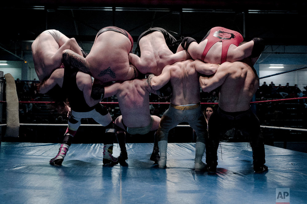 From left, wrestlers Nelson Fernandes, Alex Legrand, Ace Angel, and Zach, bottom, headlock wrestlers Lord Steven Crowley, Darkmundo, Maeven, and PV Red, fight during a wrestling charity gala in Ivry-sur-Seine, south of Paris, France on Feb. 24, 2018. (AP Photo/Kamil Zihnioglu)