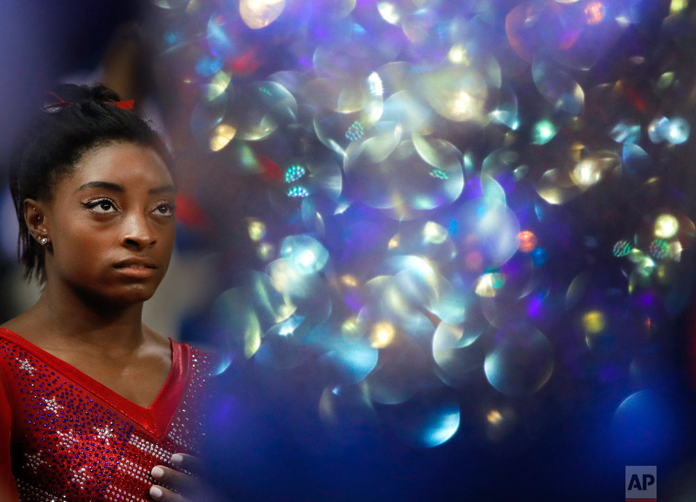 New world champion Simone Biles of the U.S. waits for the medal ceremony as the light bounces off a Russian gymnasts suit after the women's team final of the Gymnastics World Chamionships at the Aspire Dome in Doha, Qatar on Oct. 30, 2018. (AP Photo/Vadim Ghirda)