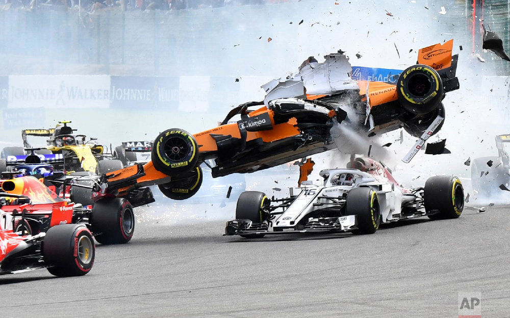 Mclaren driver Fernando Alonso of Spain, top, goes over the top of Sauber driver Charles Leclerc of Monaco as they are involved in a crash at the start of the Belgian Formula One Grand Prix in Spa-Francorchamps, Belgium on Aug. 26, 2018. (AP Photo/Geert Vanden Wijngaert)