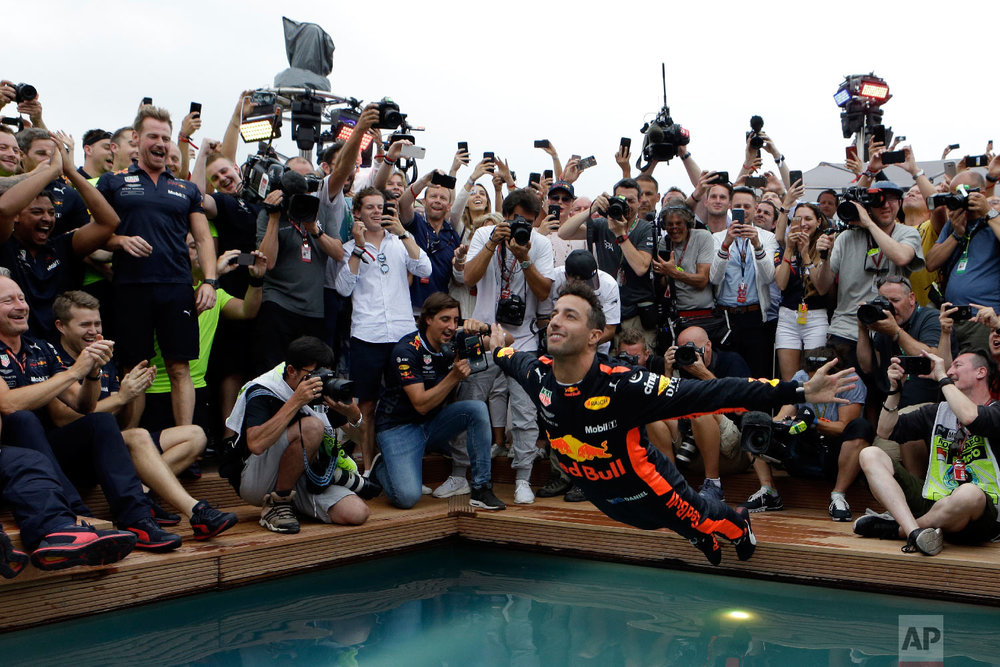 Red Bull driver Daniel Ricciardo of Australia, center, dives into a pool with his team after winning the Formula One race, at the Monaco racetrack, in Monaco on May 27, 2018. (AP Photo/Claude Paris)
