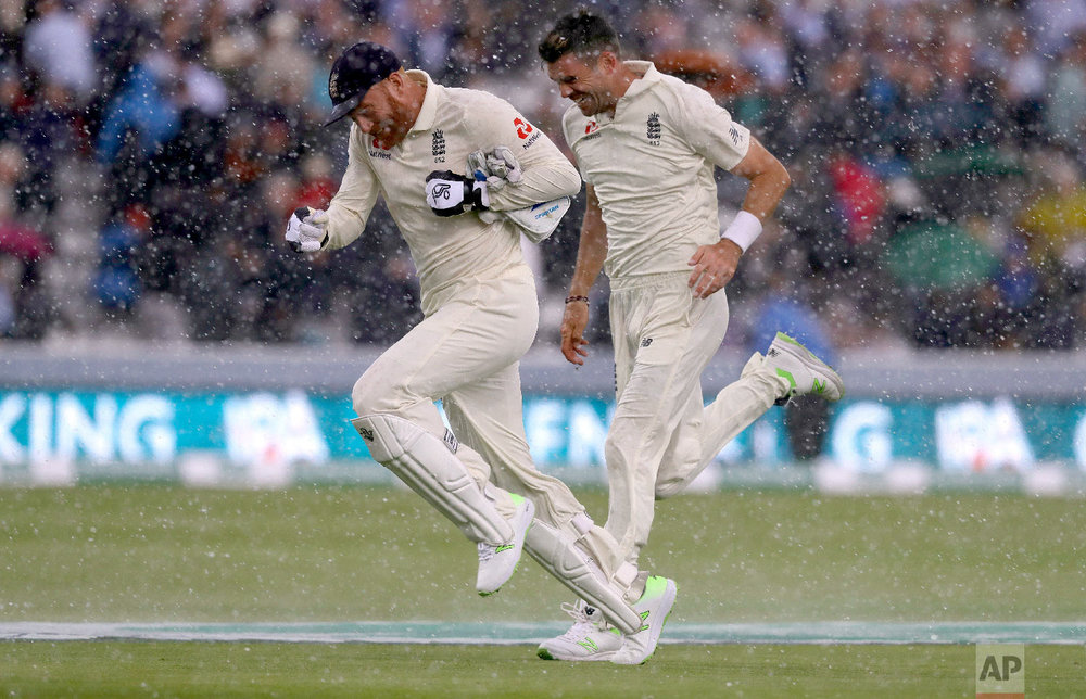 England's Jonny Bairstow and England's James Anderson run off the pitch as sudden heavy rain starts during the second day of the second test match between England and India at Lord's cricket ground in London on Aug. 10, 2018. (AP Photo/Kirsty Wigglesworth)