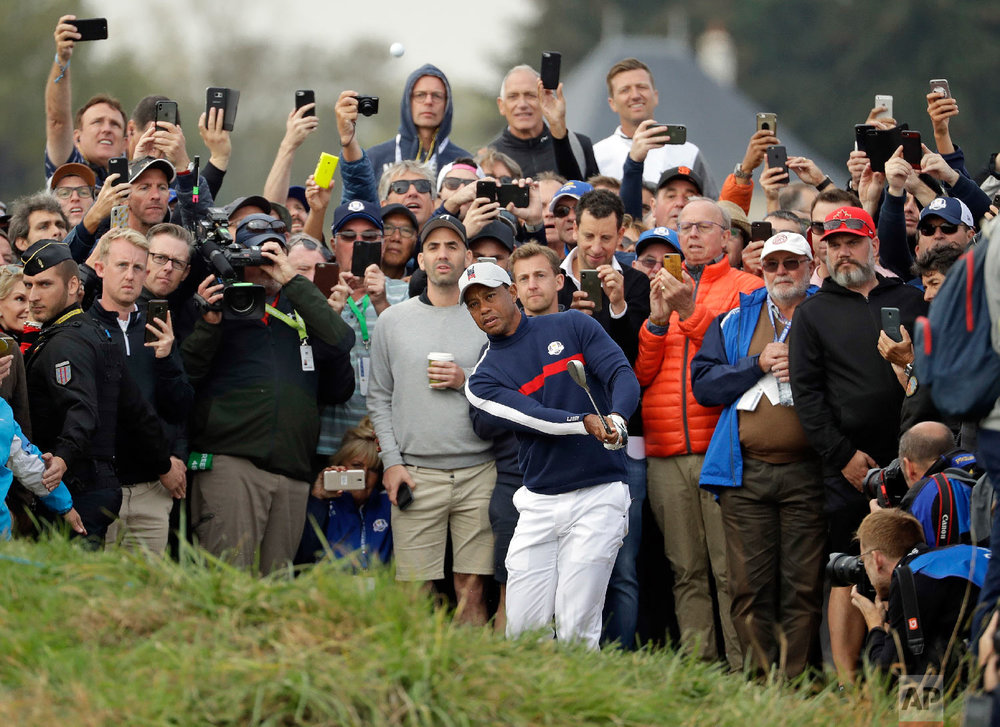 Tiger Woods of the US chips on to the 6th green during a fourball match on the opening day of the 42nd Ryder Cup at Le Golf National in Saint-Quentin-en-Yvelines, outside Paris, France on Sept. 28, 2018. (AP Photo/Matt Dunham)