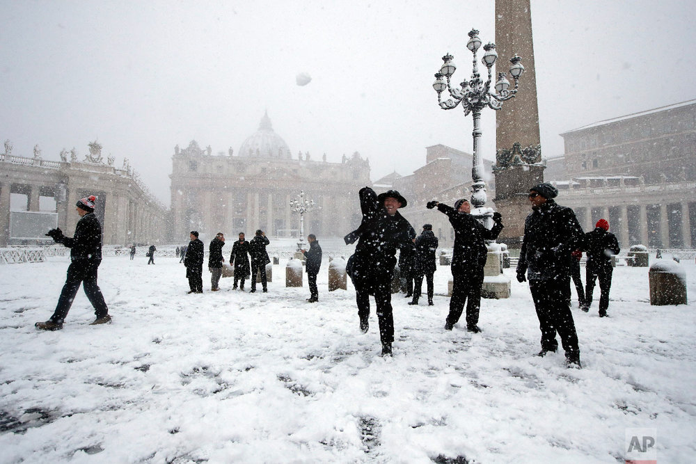 Shawn Roser, from Venice, Florida, a student at the North American college in Rome, throws a snowball as he plays in a snow blanketed St. Peter's Square, at the Vatican on Feb. 26, 2018. (AP Photo/Alessandra Tarantino)