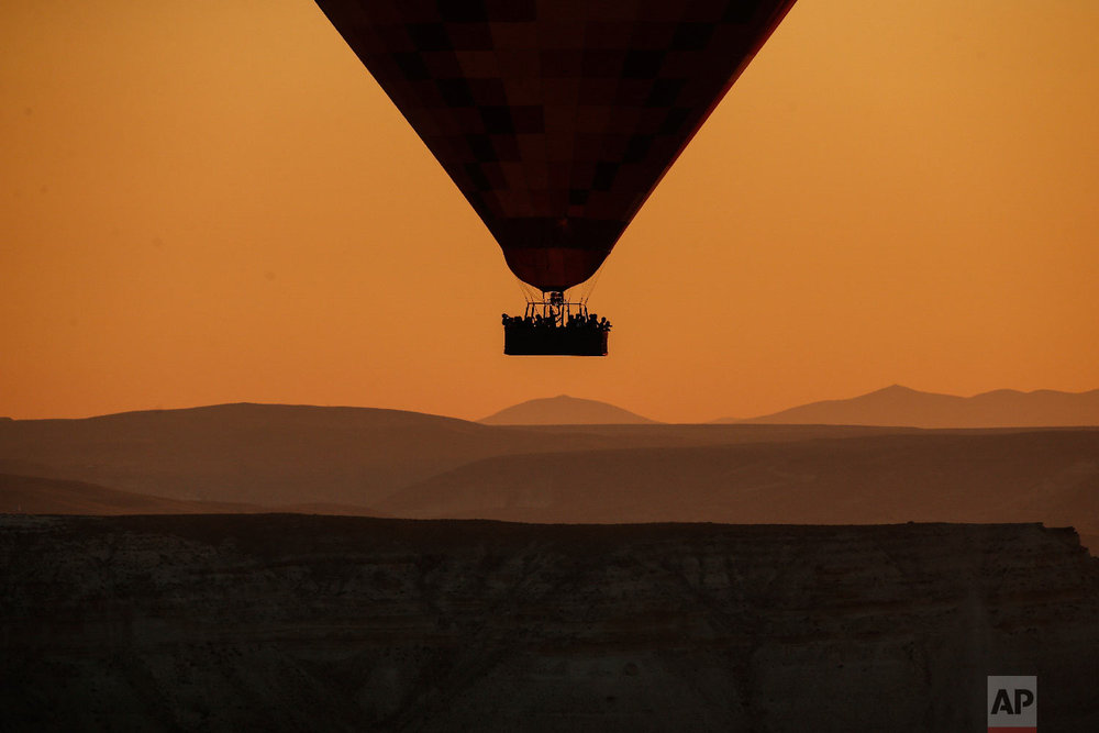 A hot air balloon, carrying tourists, rises into the sky at sunrise in Cappadocia, central Turkey on Aug. 7, 2018. (AP Photo/Emrah Gurel)