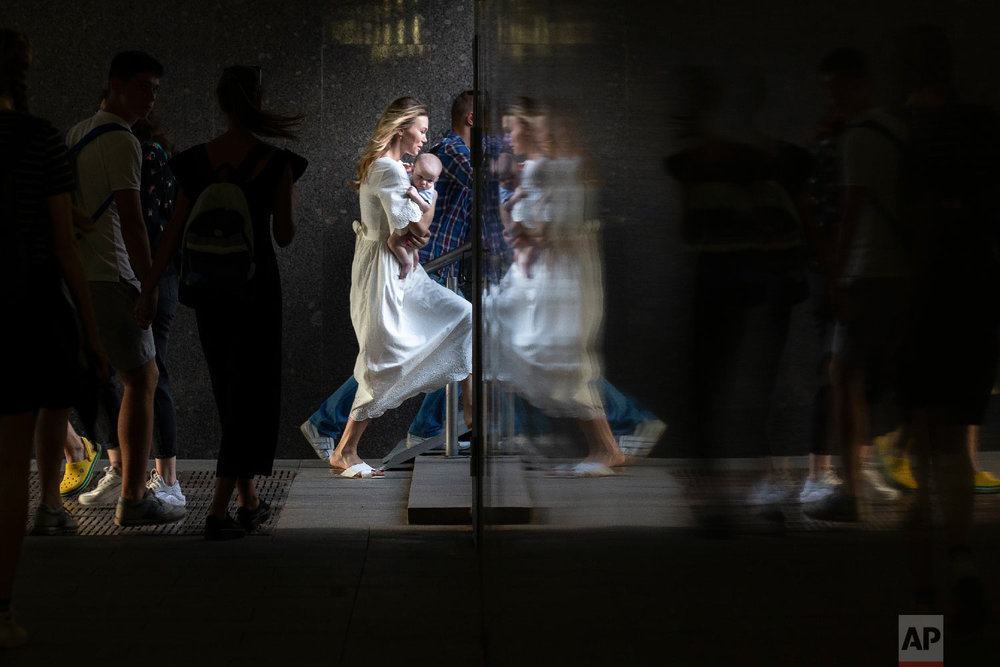 A woman carrying her child is reflected in a wall as she steps up in a subway in Moscow, Russia on Aug. 29, 2018. (AP Photo/Alexander Zemlianichenko)