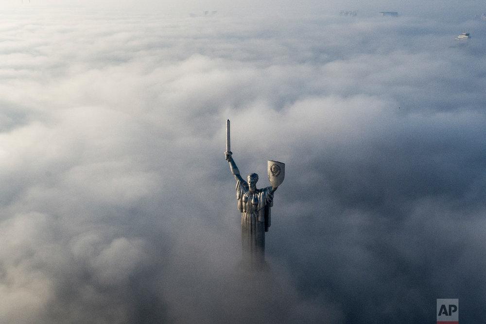 An aerial view of the WWII memorial taken through morning fog during sunrise in Ukraine's capital Kiev, Ukraine on Nov. 10, 2018. (AP Photo/Evgeniy Maloletka)