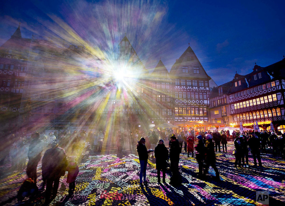 """Light shines out from one of the buildings at Roemer Square during the official opening of the """"Luminale"""" light festival in Frankfurt, Germany on March 20, 2018. (AP Photo/Michael Probst)"""