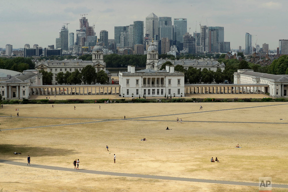 A view shows parched grass from the lack of rain in Greenwich Park, backdropped by the Royal Museums Greenwich and the skyscrapers of the Canary Wharf business district, during what has been the driest summer for many years in London on July 24, 2018. (AP Photo/Matt Dunham)