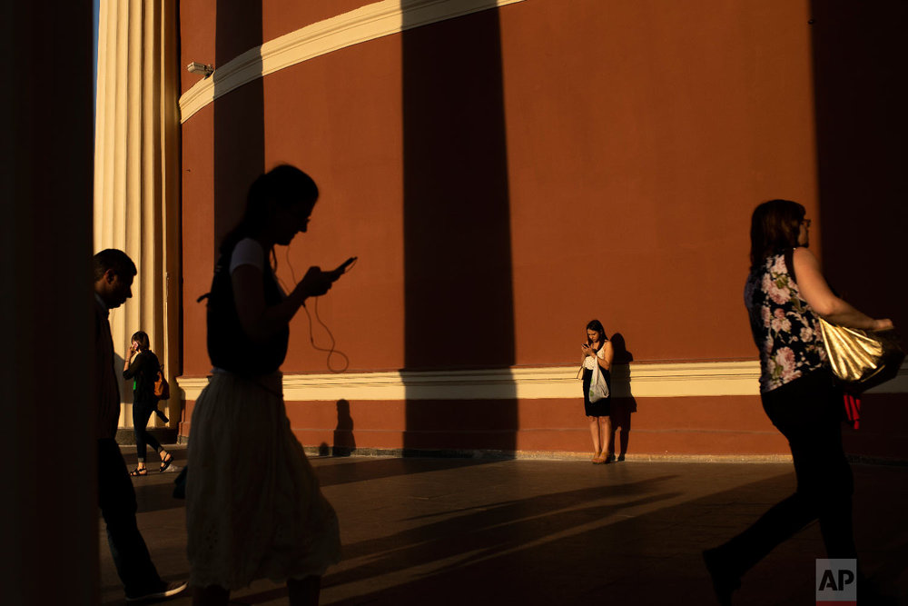 Commuters walk in and out Krasnopresnenskaya subway station in Moscow, Russia on June 22, 2018. (AP Photo/Francisco Seco)