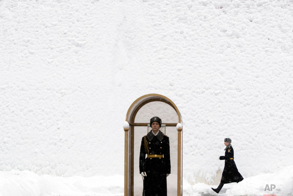 An Honor guard soldier walks along the Kremlin wall, covered by snow, as his fellow soldier stands at the Tomb of Unknown Soldier in Moscow, Russia on Jan. 31, 2018. (AP Photo/Pavel Golovkin)