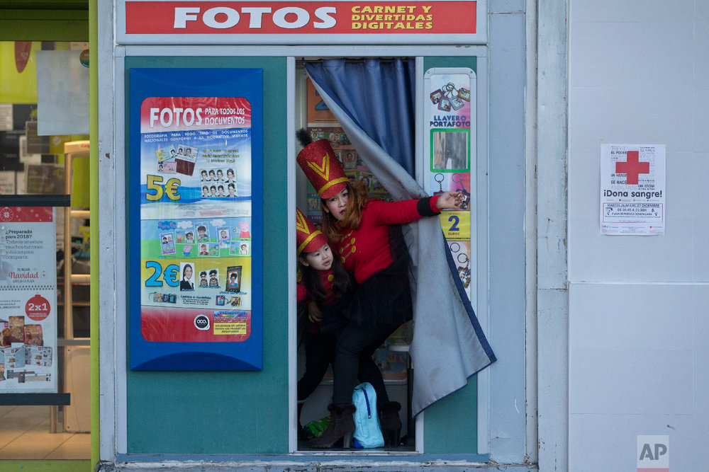 """A woman and young girl, dressed in costumes step out from a photo booth before taking part in a """"Cabalgata de Reyes,"""" Epiphany parade, in Madrid, Wednesday, Jan. 3, 2018. (AP Photo/Paul White)"""
