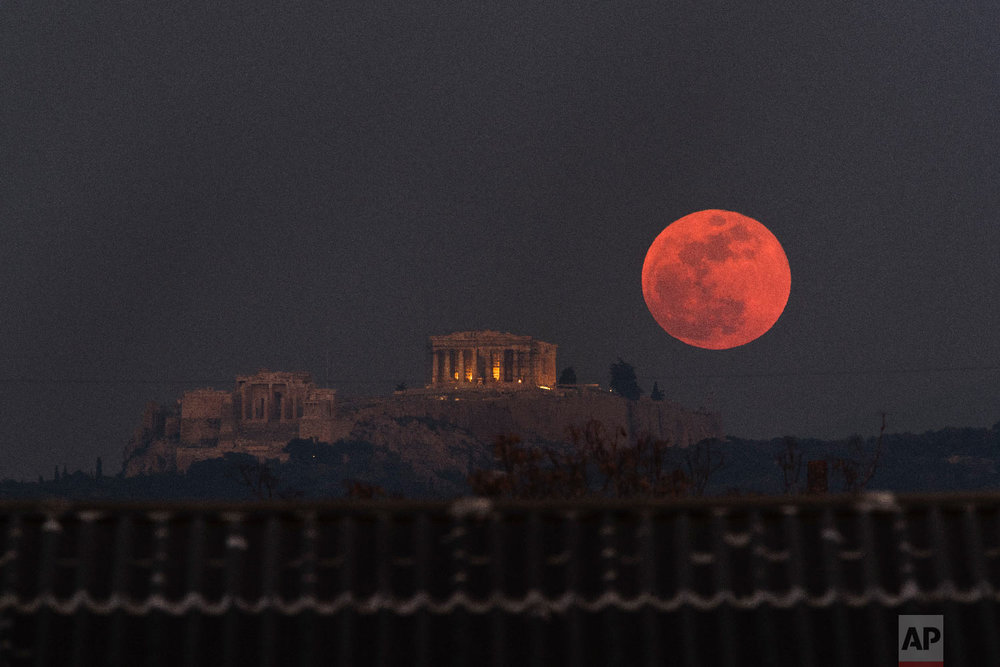 A super blue blood moon rises behind the 2,500-year-old Parthenon temple on the Acropolis of Athens, Greece on an. 31, 2018. (AP Photo/Petros Giannakouris)