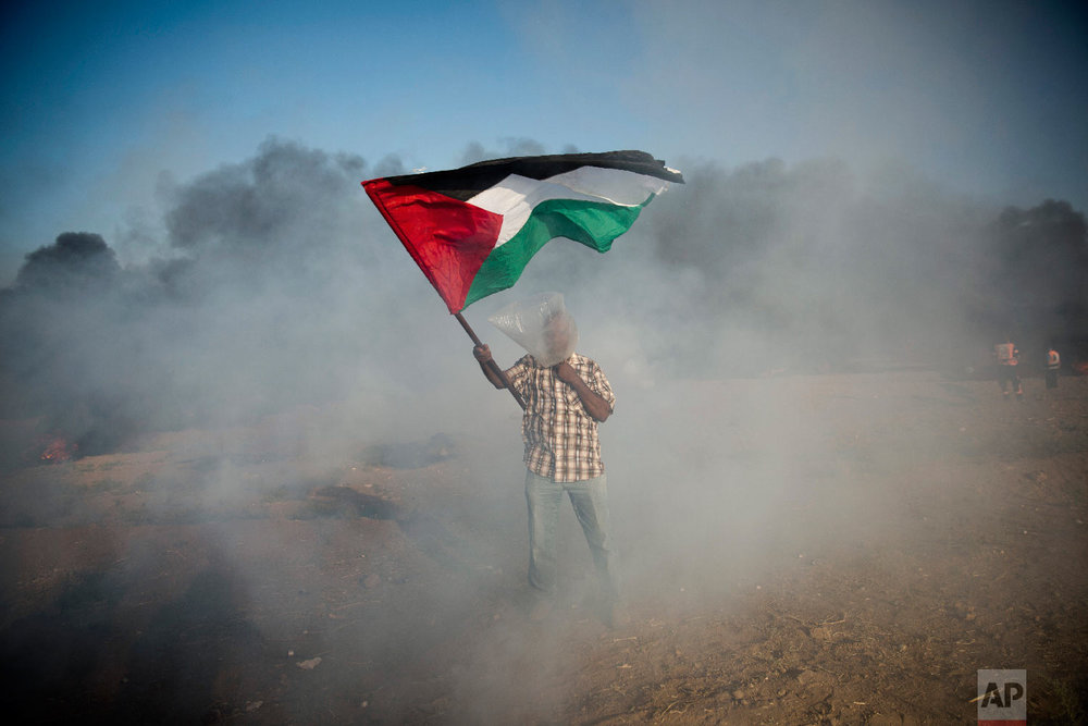 A Palestinian protester wears a plastic bag on his head as a protection from teargas, waves a national flag during a protest at the Gaza Strip's border with Israel, Aug.10, 2018. (AP Photo/Khalil Hamra)